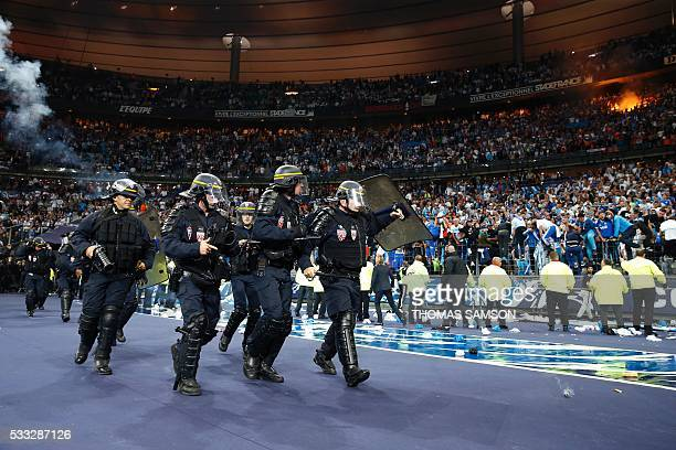 Riot police use their shields for protection near Marseille supporters in the tribunes after the French Cup final football match beween Marseille and...