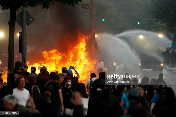 Riot police use water cannon against protesters who have set barricades alight on July 7 2017 in Hamburg northern Germany where leaders of the...