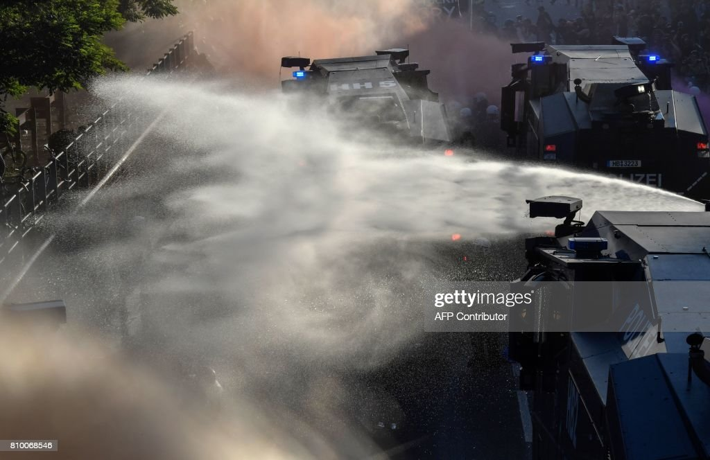 Riot police use water cannon during the 'Welcome to Hell' rally against the G20 summit in Hamburg, northern Germany on July 6, 2017. German police and protestors clashed at an anti-G20 march, with police using water cannon and tear gas to clear a hardcore of masked anti-capitalist demonstrators, AFP reporters said. / AFP PHOTO / John MACDOUGALL