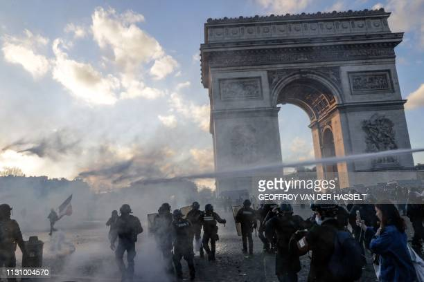 Riot police uses a water cannon to disperse protesters at the Arc de Triomphe on the Place de l'Etoile in Paris on March 16 during clashes with...