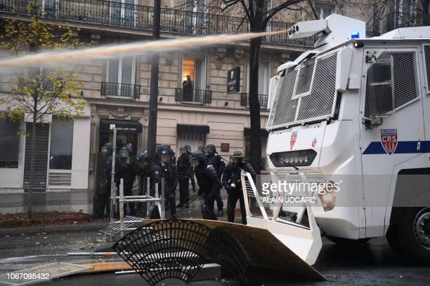 Riot police uses a water cannon to scatter demonstrators during a protest of Yellow Vests against rising oil prices and living costs on the Champs...