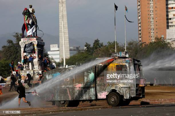 Riot police vehicle fires cannon water to demonstrators during the ongoing protests against the government of President Sebastian Piñera on November...