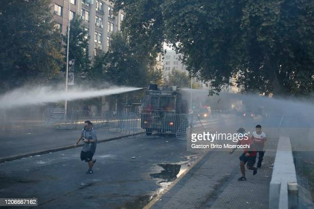 A riot police vehicle fires water to demonstrators during protests against the government of Sebastián Piñera on its second anniversary on March 11...