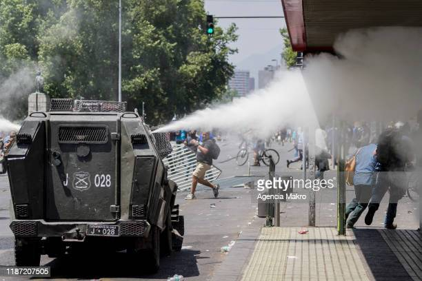 Riot police vehicle throws gas to protesters during a national strike and general demonstration called by different workers unions on November 12,...