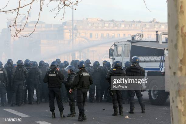 A riot police vehicle uses a water canon to disperse protesters during a Yellow vest antigovernment demonstration on February 16 2019 in Paris on...