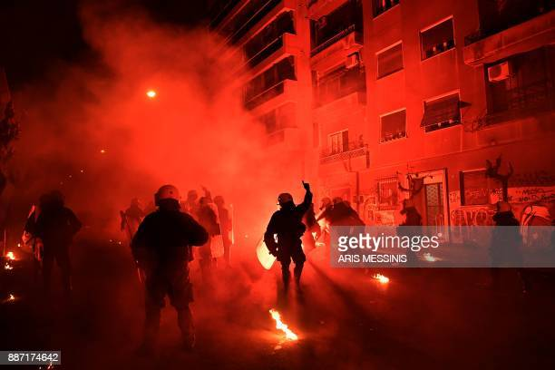 Riot police walk among small blazes during clashes with protesters in central Athens on December 6 after a demonstration commemorating 15yearold...