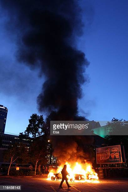 Riot police walk in front of two buring police cars on June 15 2011 in Vancouver Canada Vancouver broke out in riots after their hockey team the...