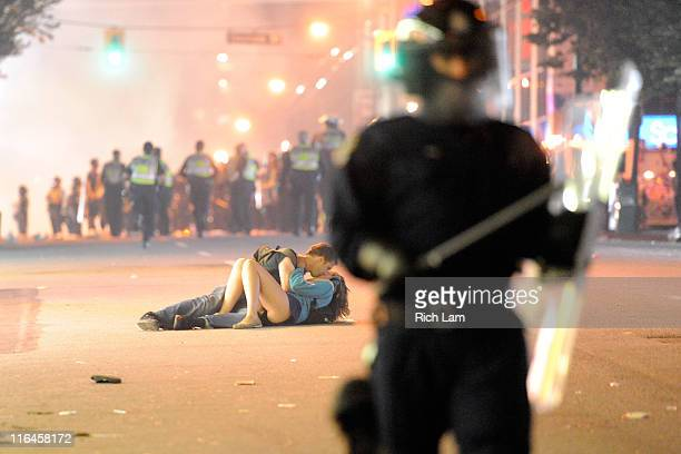 Riot police walk in the street as a couple kiss on June 15 2011 in Vancouver Canada Vancouver broke out in riots after their hockey team the...