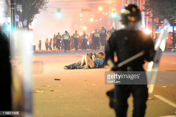 Riot police walk in the street as a couple kisses on June 15 2011 in Vancouver Canada Vancouver broke out in riots after their hockey team the...