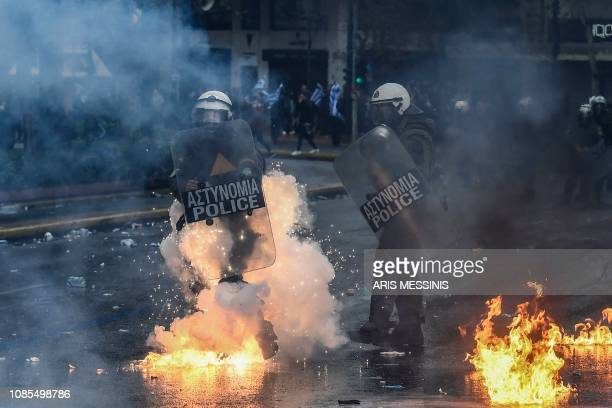 A riot police walk on fire during a demonstration against the agreement with Skopje to rename neighbouring country Macedonia as the Republic of North...