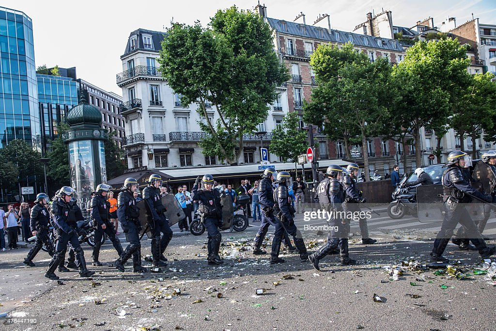 Riot police walk over broken glass bottles and debris littering a road as French cab drivers protest against Uber Technologies Inc.'s car sharing service in Paris, France, on Thursday, June 25, 2015. French taxi drivers are on indefinite nationwide strike as they demand a government crackdown on what they say is Uber's use of unlicensed chauffeurs for its UberPop service. Photographer Balint Porneczi/Bloomberg via Getty Images