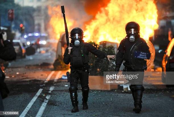Riot police walk past burning garbage containers during heavy clashes with demonstrators during a 24hour strike on March 29 2012 in Barcelona Spain...