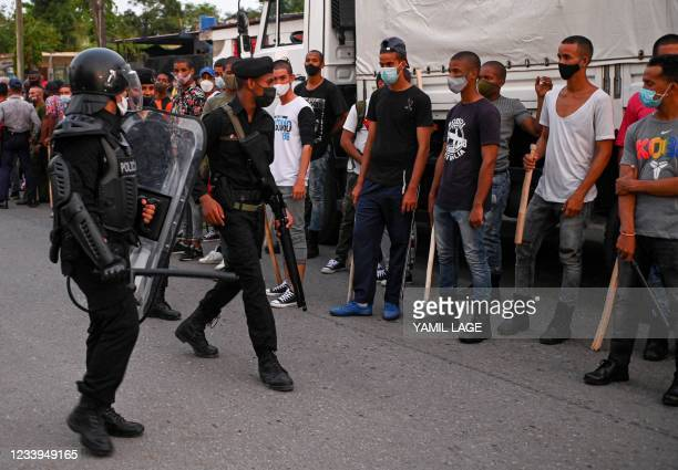Riot police walk the streets after a demonstration against the government of President Miguel Diaz-Canel in Arroyo Naranjo Municipality, Havana on...