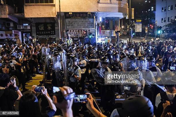 Riot police walk towards a crowd of protestors to gain ground on a bloacked road in Hong Kong early on November 7, 2016. Hong Kong police used pepper...