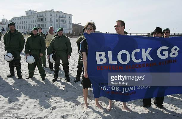 Riot police watch as protesters demonstrate against the G8 nations at the beach at the German resort town of Heiligendamm which will host the...