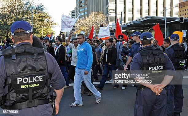 Riot police watch on as Indian students rally against racism in Sydney on June 7 2009 after a series of highly publicised attacks on Indian students...