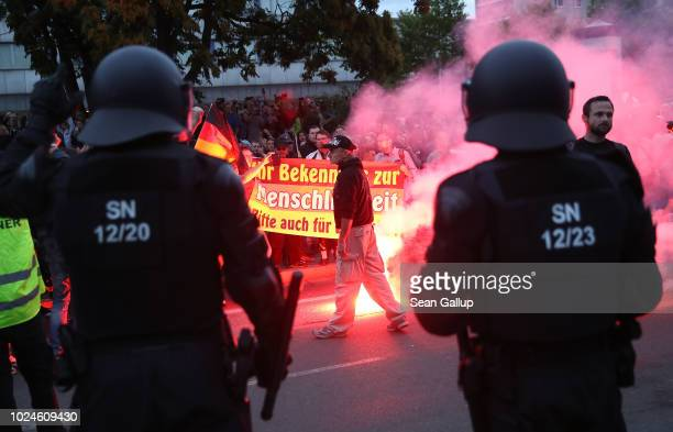 Riot police watch right-wing supporters who had gathered the day after a man was stabbed and died of his injuries on August 27, 2018 in Chemnitz,...