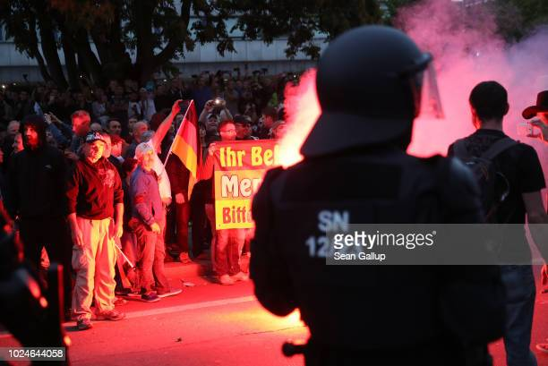 Riot police watch rightwing supporters who had gathered the day after a man was stabbed and died of his injuries on August 27 2018 in Chemnitz...