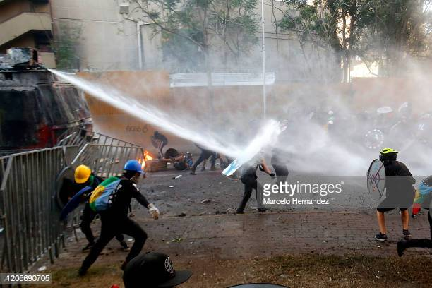 Riot police water cannon shoots water to demonstrators during a protest against the government of Sebastian Piñera on March 6, 2020 in Santiago,...
