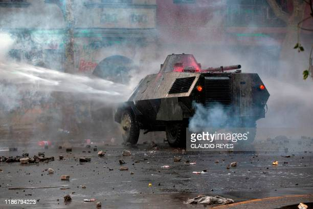 TOPSHOT A riot police water cannon sprays during clashes with demonstrators protesting against the government of Chilean President Sebastian Pinera...