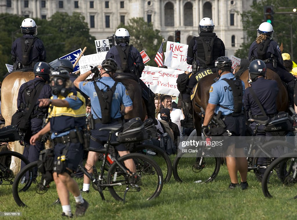 Riot police wearing gas masks block a protest march to the Republican National Convention at the Xcel Center in St. Paul, Minn., on Thursday, Sept. 4, 2008. In the background is the Minnesota state capitol building.
