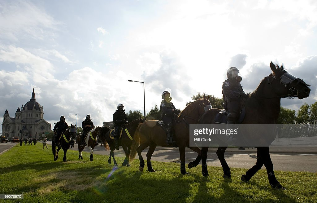 Riot police wearing gas masks on horseback move into position to block a protest march to the Republican National Convention at the Xcel Center in St. Paul, Minn., on Thursday, Sept. 4, 2008. In the background is the Cathedral of Saint Paul.