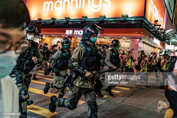 Riot police wearing protective masks charge on a street during a demonstration in Mongkok district on May 10 2020 in Hong Kong China Since the worst...