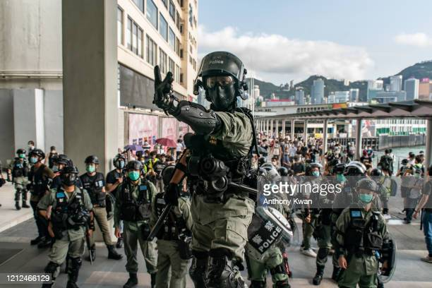 Riot police wearing protective masks stand guard during a demonstration outside a shopping mall on May 10 2020 in Hong Kong China Since the worst of...