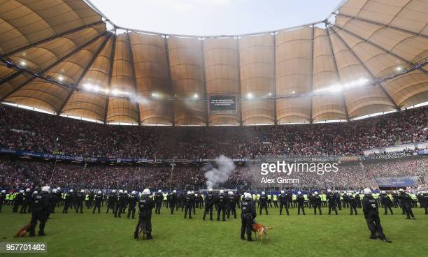 Riot police with dogs are seen on the pitch as fans of Hamburg burn flares during the Bundesliga match between Hamburger SV and Borussia...