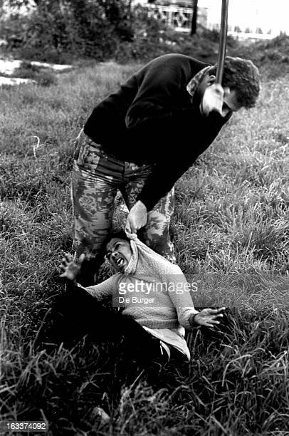 A riot policeman beats a young person in 1976 in Cape Town South Africa