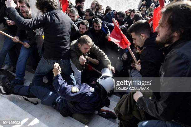 TOPSHOT A riot policeman falls while leftist protesters clash with police as they try to take the stairs leading to the parliament building in Athens...