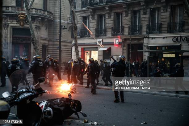 A riot policeman fires a teargas shell in Paris on January 5 during an antigovernment demonstration called by the yellow vest 'Gilets Jaunes'...