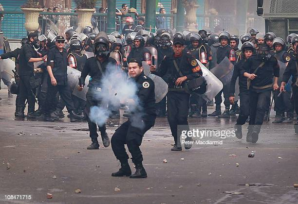 A riot policeman fires tear gas at protestors in front of the lIstiqama Mosque in Giza on January 28 2011 in Cairo Egypt Thousands of police are on...