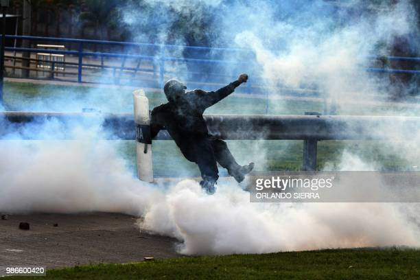 TOPSHOT A riot policeman fires tear gas to supporters of Honduran opposition leader Manuel Zelaya a former president ousted by the military as they...