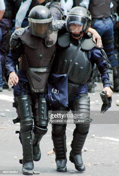 A riot policeman is helped by a colleague after an opposition protest in San Cristobal Venezuela on February 12 2015 Opposition students marched...