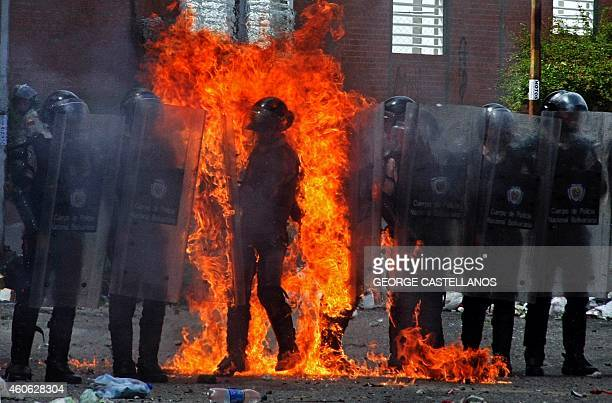 A riot policeman is set on fire by a molotov cocktail thrown by a small group of antigovernment protesters during clashes in San Cristobal Venezuela...