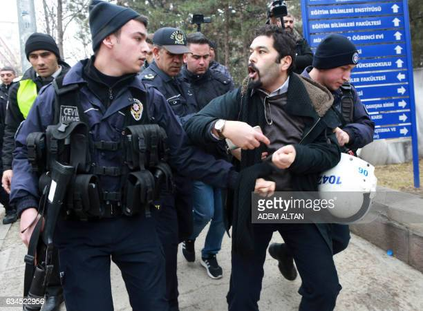 A riot policeman looks at a demonstrator who is detained as Turkish riot police intervene during a protest outside a university campus in Ankara on...