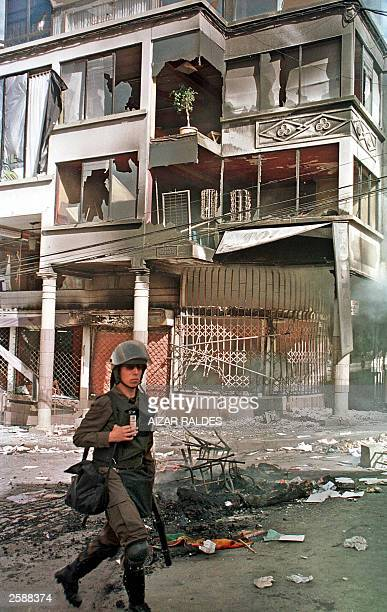 A riot policeman passes in front of a buiding set ablaze by demonstrators 13 October 2003 in downtown La Paz Five people were killed and several...