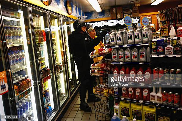 A riot policeman shops in a convenience store after a protest against the G20 Summit early on September 25 2009 in Pittsburgh Pennsylvania Riot...