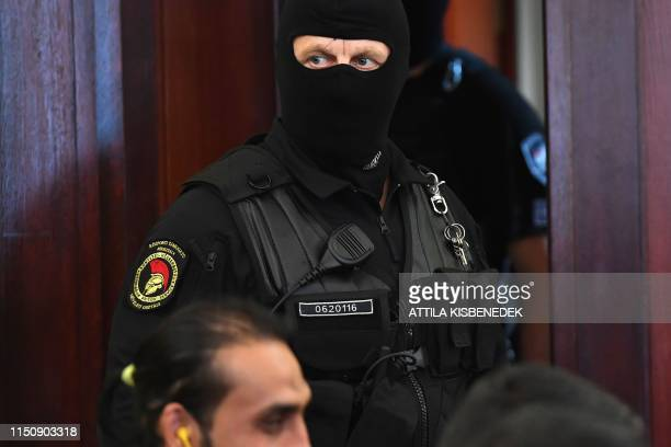 Riot policeman stands guard during the final verdict in the trial of smugglers for the gruesome deaths of 71 migrants who suffocated in a lorry...