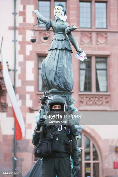 A riot policeman stands in front of a fixed Guy Fawk mask at the fountain figure of Justice Fountain during the Blockupy protests on May 17 2012 in...