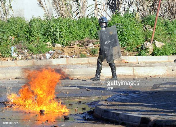 A riot policeman stands near fire during clashes with locals in the western suburb of Cheraga in Algiers on January 31 2012 following a court...