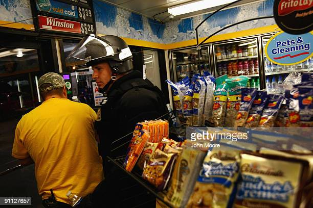 A riot policeman stops in a convenience store after a protest against the G20 Summit early on September 25 2009 in Pittsburgh Pennsylvania Riot...