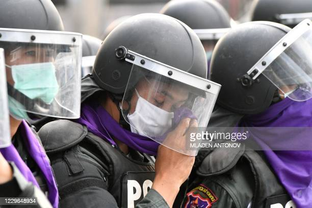 Riot policeman wipes his eyes as tear gas is fired during an anti-government rally by pro-democracy protesters in Bangkok on November 17, 2020.