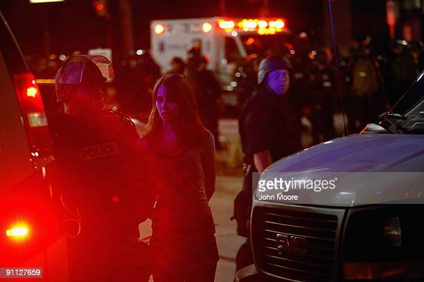 Riot policemen arrest a woman detained during a protest against the G20 Summit early on September 25 2009 in Pittsburgh Pennsylvania Riot police with...