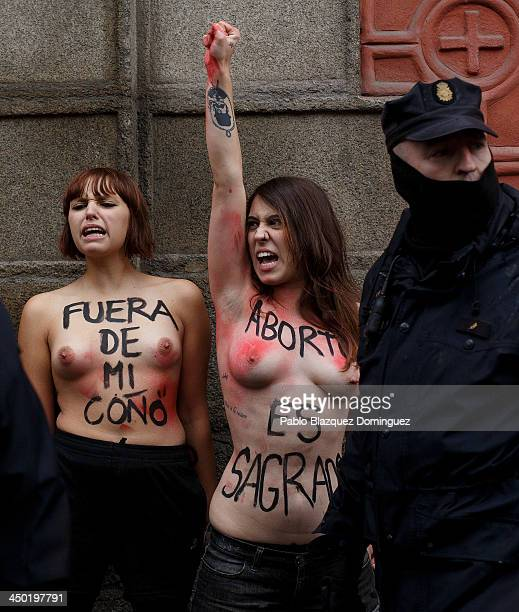 Riot policemen arrest FEMEN group activist with body paintings reading 'get out of my vagina' and 'abortion is sacred' as a ProLife demonstration...