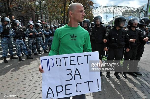 Riot policemen block a suporter of former Prime Minister of Ukraine Yulia Tymoshenko holding placard that reads Protest for arrest near the...