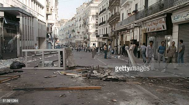 Riot policemen deploy in the streets of Algiers 10 October 1988 and one of them fires tear as Security forces shot dead at least 25 people during its...