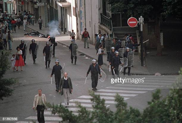 Riot policemen deploy in the streets of Algiers as one of them fires tear gas Security forces shot dead at least 25 people during its...