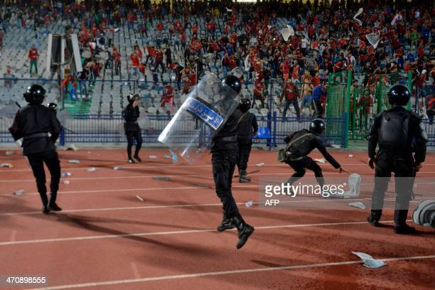 Riot policemen deploy themselves during clashes with supporters after Egypt's AlAhly won the African Super cup final football match against Tunisia's...